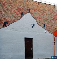 Muurschildering met silhouetten van bergbeklimmers op een oude gevel