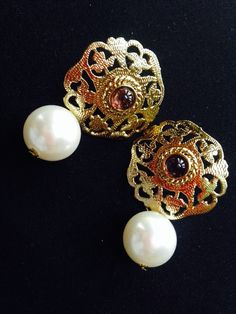 Golden studs with droping pearl.