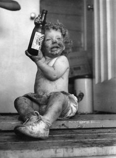 """Dirty baby brandishing beer bottle, Calgary, Alberta.  from the """"Children at Play"""" set from the flickr stream of the Glenbow Museum"""