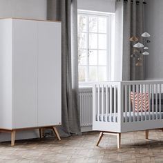armoire design enfant blanche avec pieds en bois façon compas et lit à barreaux blanc avec pied en bois compas. Mobilier design et moderne pour une chambre d'enfant