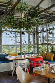 Diseño de restaurantes: mesa en el restó del 25 Hours Hotel Berlín, con gran corona tipo rejilla llena de plantas colgantes.