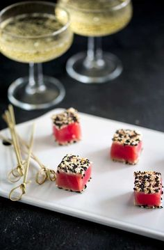 Over head shot of Seared Sesame Tuna bites, sat on a white platter, with bamboo skewers on the side.