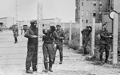 August 14 1961: Soldiers of the East German National People's Army (NVA) erecting barbed wire fences to close off a street in preparation for the construction of the Berlin Wall. The first concrete emplacements were erected on August 17.