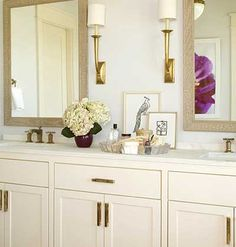 love the brass fixtures and hardware. sconces. and pop of color from artwork in mirror reflection. sophisticated bath + simple styling.