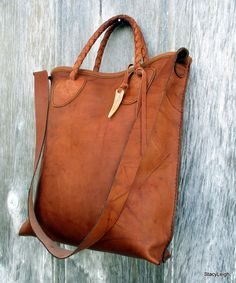 Leather tote bag with a shoulder strap made from Saddle Montana leather. It is a smooth leather with marbled character and darker veins throughout in a tobacco brown shade. The bag is fully lined with 3 leather, drop in pockets. The bag is 14 tall by 12.5 across with a 3 bottom. It has a shoulder strap and 2 short, round braided handles for carrying options. Snap closure. The bag has a leather tassel and a genuine, deer antler tip. Handmade.
