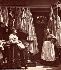 An Old Clothes Shop in St Giles: 'As a rule, secondhand clothes shops are far from distinguished in their cleanliness, and are often the fruitful medium for the propagation of fever, smallpox '; John Thompson, photographer, 1876, London.