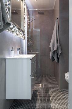 Pieni kylpyhuone on saatu toimivaksi ja tyylikkääksi puutalon remontin yhteydessä. Seinät on päällystetty betonimaisella mikrosementillä ja lattiat tummilla mosaiikkilaatoilla. Kauniisti valaistu, suuri hopea peili toimii katseenkiinnittäjänä sekä tuo glamouria ja ylellistä fiilista kylpyhuoneeseen.