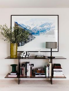 In a London apartment, interior designer Sophie Ashby carved an entryway nook with a well-styled tinted glass console and a statement piece of art, proving that you don't need a ton of space to do...