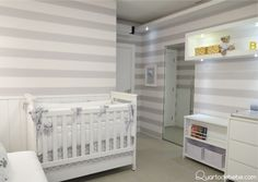 Quarto de bebê com berço e enxoval branco com detalhes de lacinhos, caixas organizadoras e papel de parede listrado
