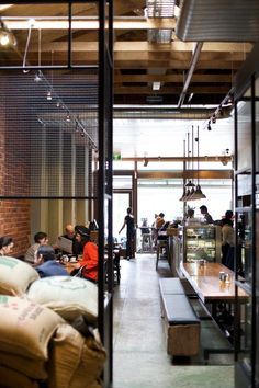 Open roof, long communal tables, elongated interior, lines at right angles, screens and division