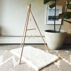 This is a wooden teepee gym that has a wooden bead mobile for entertaining  little minimalistic babies. There is no coating on the wood to prevent any  toxic exposure.  The gym measures 2.5 feet high  If you would like a custom order. Please message me!  Gym is to be used with parental supe