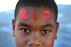 Jordan Puckett, age 10, shows off his painted forehead honoring Mike Brown during a gathering of people on the QuikTrip lot on Thursday, Aug. 14, 2014. (David Carson/St. Louis Post-Dispatch)