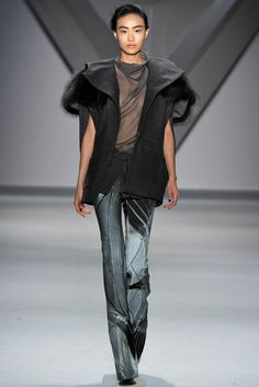 Charcoal melton oversized sleeveless jacket with raccoon collar over steel silk chiffon cowl neck halter top with column print faille flared pant and charcoal melton zip-front peplum.