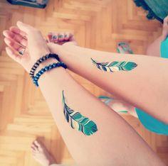 Matching Indian feather tattoos via Popovicka