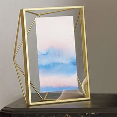 "new angle.  Prismatic structure frames your favorite photos with new dimension.  Handcrafted of brass-powdercoated steel, metallic rods angle a geometric form that freestands vertically or horizontally to float a 4""x6"" in clear glass. HandmadeBrass-powdercoated steelGlass display paneHolds a 4""x6"" photoFreestands horizontal or verticalPackaged in giftable box."