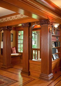 Surprising neoclassical columns in mahogany support beams in the entry hall with keystone arches between them, lending a formal air and creating an inviting seating nook. 1909 bungalow in Portland, OR