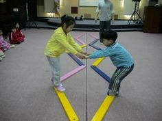Gross motor activity: kids hold each others hands and try to help each other across the balancing beam