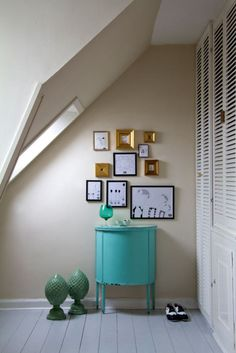 lovely little vignette of black and gold frames with a pop of turquoise