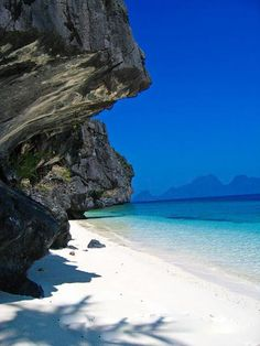 Karst limestone cliffs on a white sand island beach in Palawan beside blue water, near El Nido, Philippines.