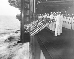 November 26, 1944: Burial at sea ceremonies are held aboard the USS Intrepid for members of the crew lost after the carrier was hit by a Japanese suicide pilot while operating off the coast of Luzon, the Philippines, during World War II. Sixteen men were killed in the kamikaze attack. (AP Photo/U.S. Navy)