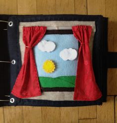 The Quiet Book Blog: Katie's Quiet Book - weather page.  The weather pieces are stored in a pocket on a separate page and they velcro on and off of the window. I like the curtains a lot!
