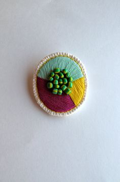 Colorful geometric brooch embroidered green violet and yellow with green and yellow African beads Spring fashion. $35,00, via Etsy.