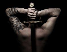 Muskelmann mit Schwert und Tattoo