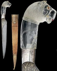 Indian (North, Mughal) kard (straight dagger), 18th century, watered steel blade damascened with gold with floral sprays near the hilt,  rock crystal lion's head hilt, carved mane, a stylised chain and collar around the neck, eyes inset with coloured stones, a foiled beryl in the centre of its forehead, ruby tongue, velvet-covered sheath with gilt-copper mounts each engraved with floral lattice designs below the pierced cusped border, ball finial, 15½in. (39.3cm.) long.