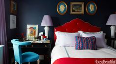Nick Olsen designed a Moorish arched headboard in shiny red leather with lavender piping to contrast with the bedroom's matte walls in Fine Paints of Europe Eurolux Interior Matte in Navy Blue. A Directoire-style desk doubles as a night table. Vintage chair covered in a suede from Global Leathers. Bed linens, Frette.