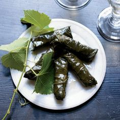 "Stuffed Grape Leaves with Pork and Fregola | David Page and Barbara Shinn of Shinn Estate Vineyards on the North Fork of Long Island trim tender young grape leaves and brine them at home. Page often stuffs the brined leaves with sausage made from locally raised duck, calling the hors d'oeuvres ""a NoFo classic."" Here, he creates a version with ground pork and fregola, a small, round Sardinian couscous."