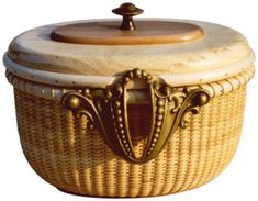"Nantucket Bureau Basket  7"" x 9"" x 7""    Nantucket style basket woven of cane over cane staves with cherry base and reed rim. The lid is of pine topped with a cherry disk and rimmed in reed."