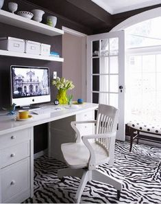 White office with a wow. Big window, attractive door, zebra pattern rug and dark brown walls and ceiling molding.