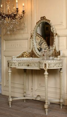 A low hanging chandelier illuminates this pretty vanity...