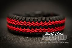 """Black trilobite 550 paracord bracelet with red micro cord stitching and 5/8"""" contoured side release buckle. 550 Nylon Paracord Colors: Solid Color Chart: Rose pink, salmon pink, hot pink, fuscia, impe"""
