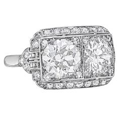 Art Deco Twin Diamond Dress Ring. Showcasing two circular-shaped brilliant-cut diamonds weighing 1.68 and 1.44 carats, in a diamond-set platinum mount, with 32 circular-cut diamond accents ~0.56 total carats.