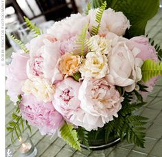 Glass cylinders were lined with ti leaves and filled with peonies, ranunculus, garden roses and ferns. Large chunky votives lit each table.