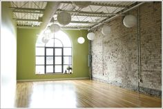 dream designs for my future yoga studio.. Love the accent wall color, the light colored exposed brick and the paper lanterns...