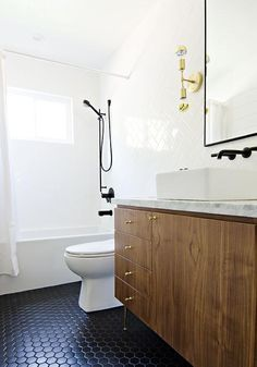 Modern bathroom features a veneer washstand adorned with brass hardware, Schoolhouse Electric Radcliffe Knobs, topped with marble fitted with a rectangular vessel sink under a Brizo Odin Faucet in Matte Black and a black metal framed mirror illuminated by Cedar Moss VIsta 2 Sconces.