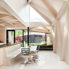 In this interior plywood is used to create this extension, which introduces geometric patterns. Having those beautiful floor to ceiling windows, you open up the kitchen and it's being linked with the gardens for an indoor-outdoor feel.