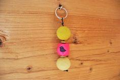 Schlüsselanhänger mit Filzkugeln in zwei unterschiedlichen Grüntönen, Holzperle in geometrischer Form in pink und zwei Holzlinsen in gold. Die geometrische Holzperle wurde von mir mit einem Vogelmotiv bestempelt (auf der Vorder- und Rückseite). Die Perlen wurden aufgefädelt auf eine schwarze Kordel. Dieser Schlüsselanhänger hat eine Länge von ca. 11 cm.