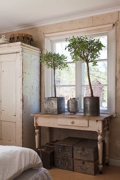 table in front of window with topiaries