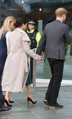 Ms Markle is pictured hand in hand with Prince Harry as they head into the Titanic Visitor...