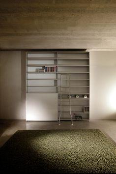 Estantería salón con escalera y puerta corredera hueco TV.