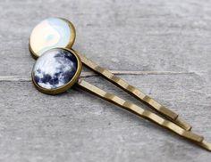 2 wunderschöne Haarklemmen mit je einem Motiv der Mondoberfläche und einem milchig, weiß schimmernden Glasstein. Dieses sieht aus, wie der Mond bei Nacht. Die Schmucksteine haben jeweils einen Durchmesser von 12 mm. Die Haarnadel ist ungefähr 7 cm lang