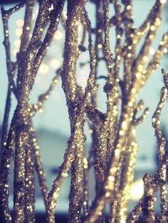 "glitter sprayed on twigs to make a ""snowy"" centerpiece. pretty pretty. .... Silver glitter"