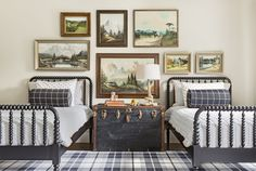 GUEST room. Twin Jenny Linds with ticking comforters. Oil painting scenes gallery. Trunk for bedside table and storing bed linens