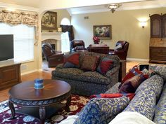 A pair of sofas fill this living room which also features a low, round coffee table. An adjacent sitting area with leather chairs by the fireplace makes the room spacious and cozy.
