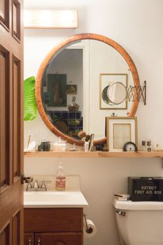 Image above: The tiniest of bathrooms felt like it doubled in size when the small medicine cabinet was removed and a large, round burlwood mirror was added. Essentials are stored on an Ikea shelf while other sundries are stored in the vintage tin first aid box. Glass Utility Jars by HomArt.