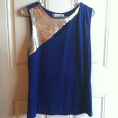 Jennifer Lopez tank, blue & silver, L Good used condition dressy/holiday top. Shiny, metallic silver sequins at the top with a tiny slit across the chest but not too low. It has a few pleats on the left shoulder. Shell: 95% Rayon, 5% Spandex. Lining: (behind sequins) 100% Polyester. Hand wash inside out, cold water, mild detergent, flat dry & cool iron if needed. Very soft, flowy top. Great for holiday parties/get togethers! Jennifer Lopez Tops Tank Tops