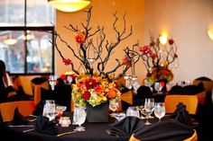 Black tablecloths with orange chair sashes set the scene, but we can't take our eyes off this dynamic centerpiece with branches, suspended candles, and bold florals.Photo Credit: Cary Pennington Photography